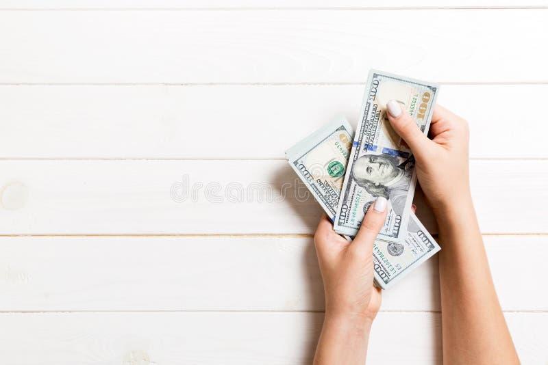 Vue d'en haut des mains d'une femme d'affaires comptant des billets de 100 dollars sur fond de bois Concept de réussite et de ric photos stock
