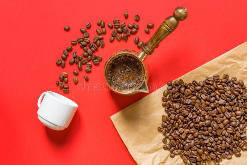 Vue d'en haut du café frais préparé dans une casserole à café turc traditionnel, tasse blanche et haricots à café sur papier d'ar image stock