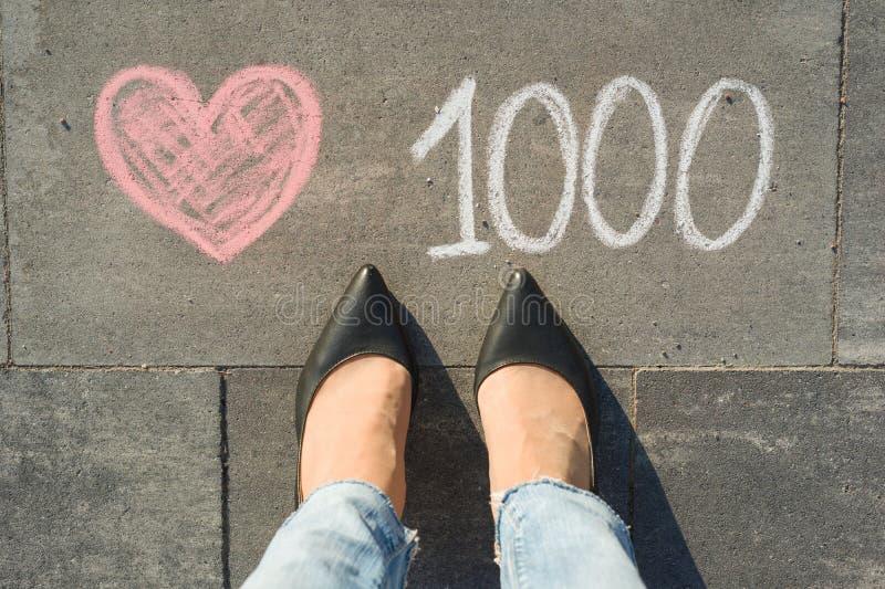 Vue d'en haut, pieds femelles avec des goûts des textes 1000 dans les réseaux sociaux écrits sur le trottoir gris photo libre de droits