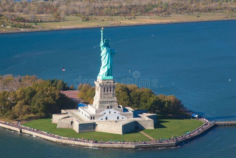 Vue d'hélicoptère de statue de la liberté Silhouette d'homme se recroquevillant d'affaires Liberty IslandManhattan, New York City image stock