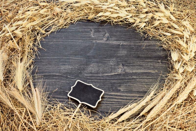 Vue d'herbe sèche de foin sur le fond en bois foncé avec l'étiquette de tableau image stock