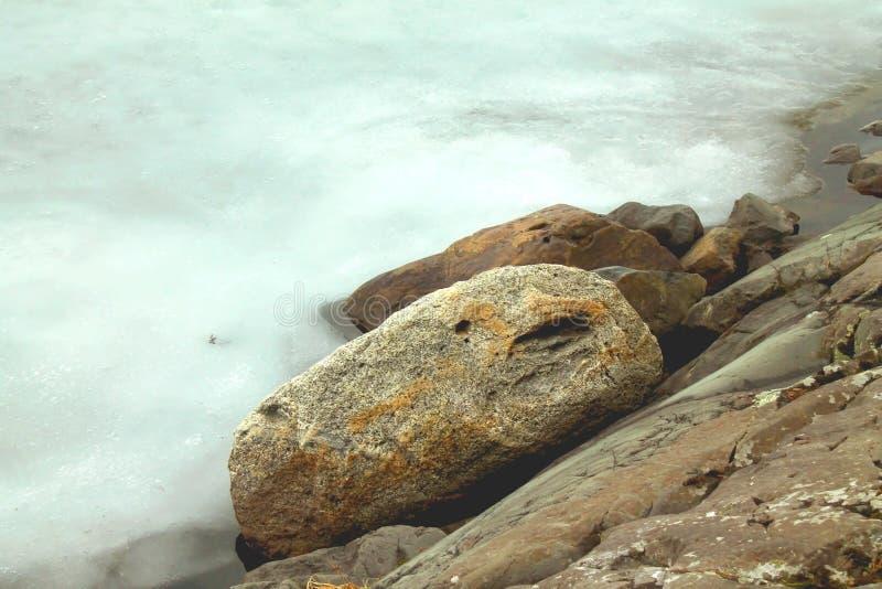 Vue d'hiver à la glace et aux roches neigeuses sur les rivages du lac glacial photographie stock libre de droits