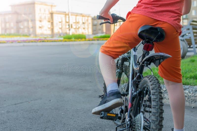 Vue d'un adolescent qui s'assied sur un vélo photographie stock