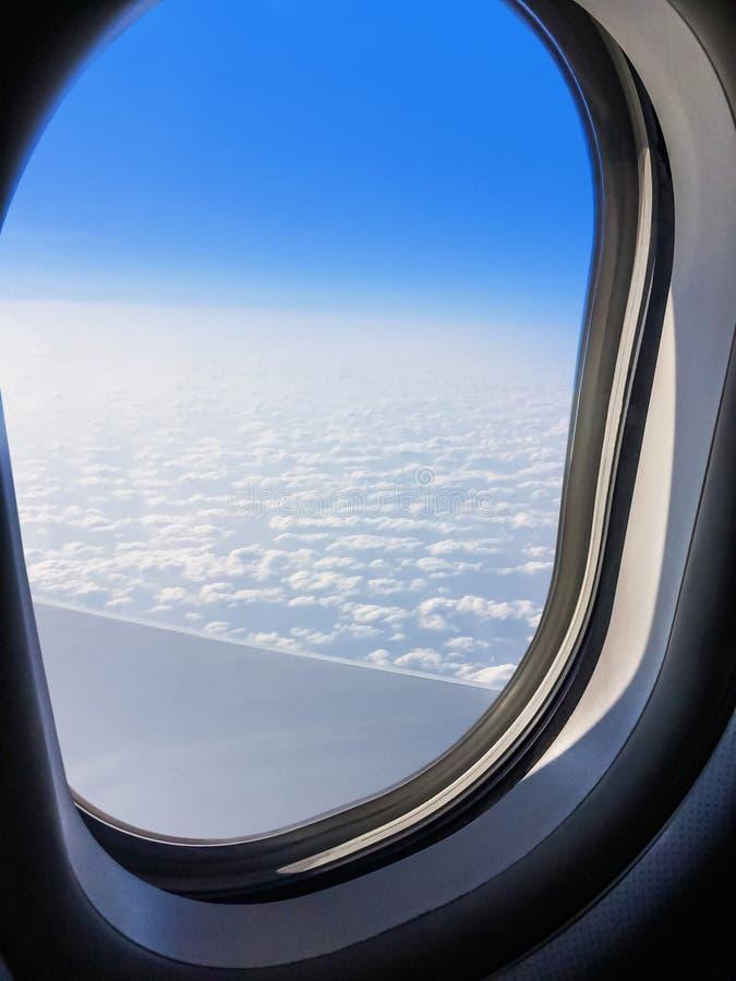Vue d'un avion commercial de fenêtre où vous pouvez voir l'aile qui pilote au-dessus des nuages photographie stock