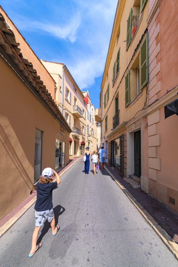 Vue d'un petit garçon dans une rue française étroite, chassant ses parents qui sont en vacances dans les Frances images libres de droits