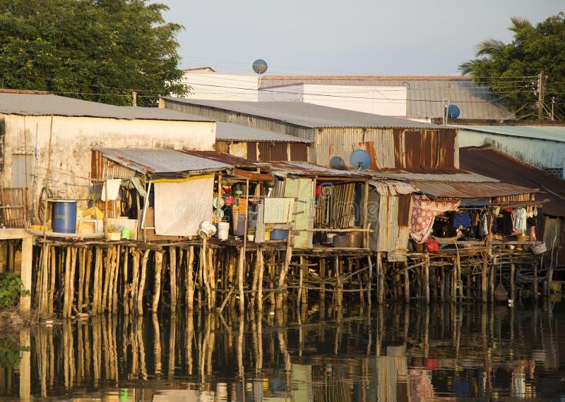 Vue d'un salon de taudis sur une rivière polluée image stock