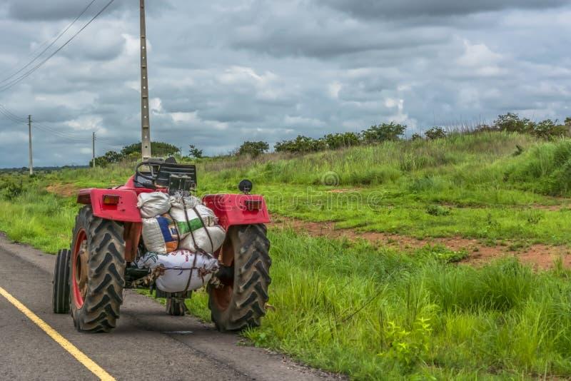 Vue d'un tracteur de ferme sur le bord de la route, paysage naturel de prairie avec des lignes électriques comme fond photo stock