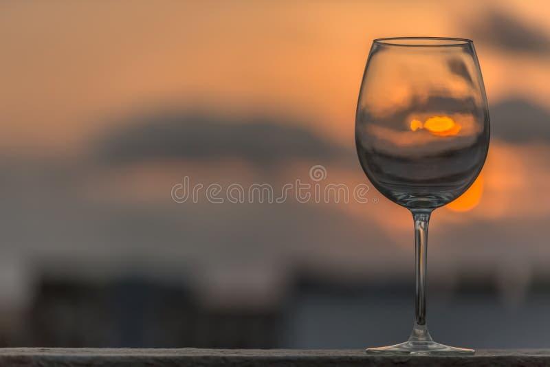 Vue d'un verre vide étonnant de vin se tenant grand, coucher du soleil comme fond photos libres de droits