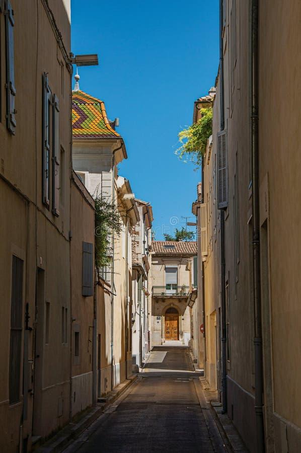 Vue d'une allée étroite avec le ciel bleu ensoleillé, au centre de la ville de Nîmes photographie stock