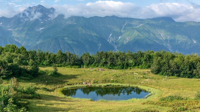 Vue d'une clairière de montagne avec un lac transparent de miroir, et montagnes de touriste et hautes avec les crêtes couronnées  image libre de droits