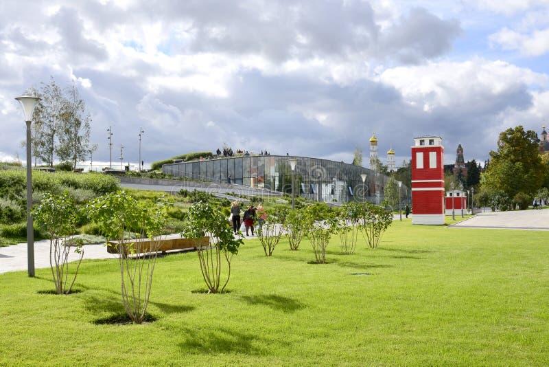 Vue d'une pelouse bien-toilettée avec les buissons lilas et d'un bâtiment rouge lumineux en parc de Zaryadye photo libre de droits