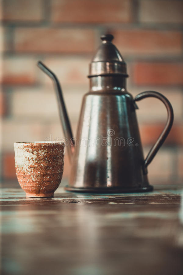 Vue d'une tasse de café et de bouilloire de versement, fond de brique, C photo stock
