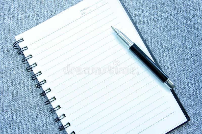 Vue de bureau avec un carnet vide avec le stylo photographie stock libre de droits