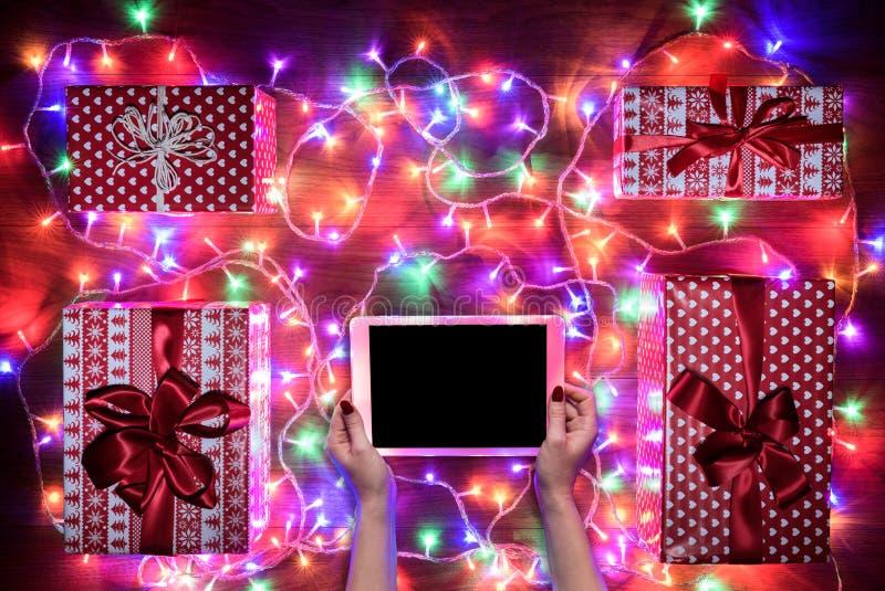 Vue de bureau de ci-dessus avec les mains femelles et le comprimé numérique, achats en ligne de Noël photographie stock