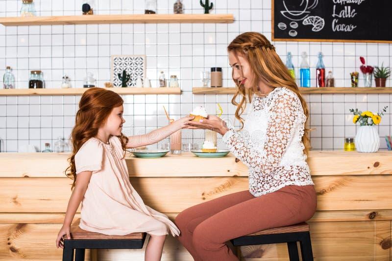 vue de côté de belle mère et de fille heureuses tenant le petit gâteau photo libre de droits