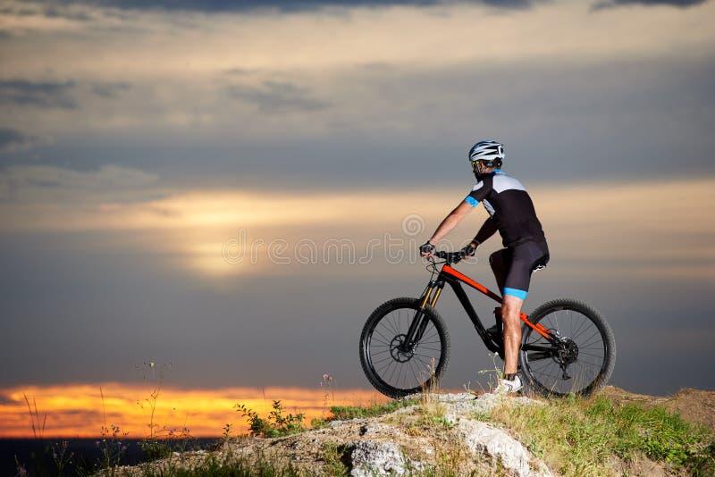 Vue de côté de cycliste sur le vélo de montagne au sommet du fond brouillé par restingwit de roche du ciel de coucher du soleil image stock