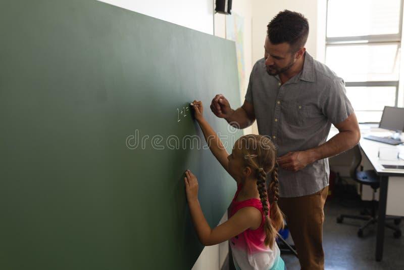 Vue de côté d'écolière avec l'écriture de professeur de maths sur le panneau de craie dans la salle de classe photo stock