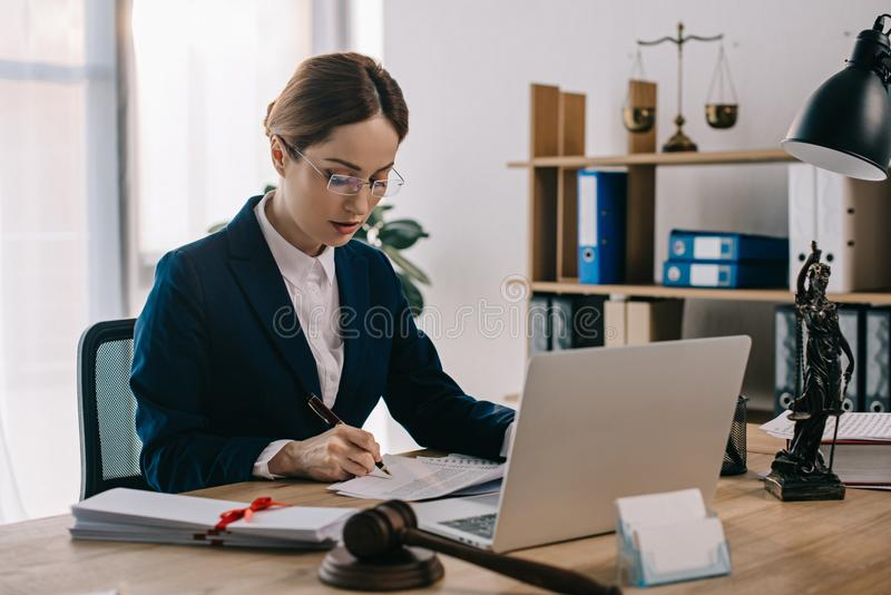 vue de côté d'avocat féminin faisant des écritures sur le lieu de travail avec l'ordinateur portable image stock