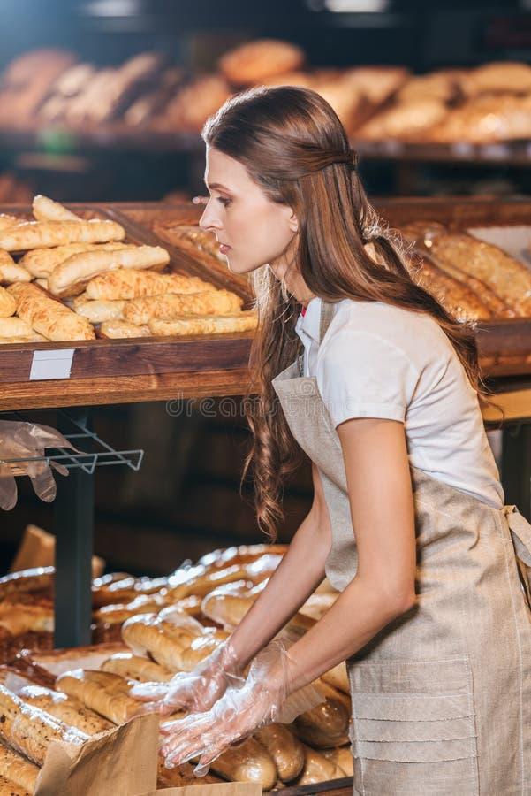 vue de côté d'employé de magasin arrangeant des pains de pain photos libres de droits