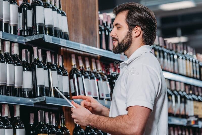 vue de côté d'employé de magasin avec le comprimé regardant des bouteilles de vin photographie stock libre de droits