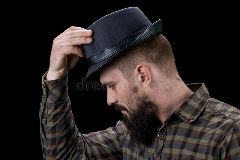 Vue de côté d'homme barbu triste avec le chapeau regardant vers le bas photos libres de droits