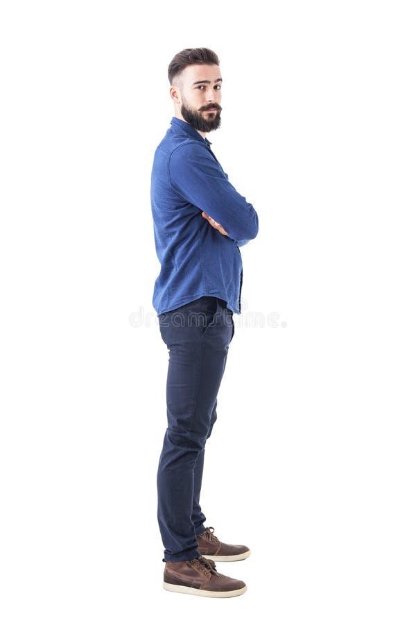 Vue de côté d'homme frais sérieux sûr avec les bras croisés regardant l'appareil-photo photos libres de droits