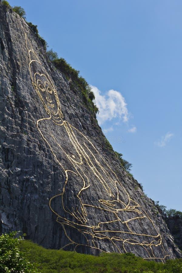 Vue de côté d'image découpée de Bouddha sur la falaise photographie stock libre de droits