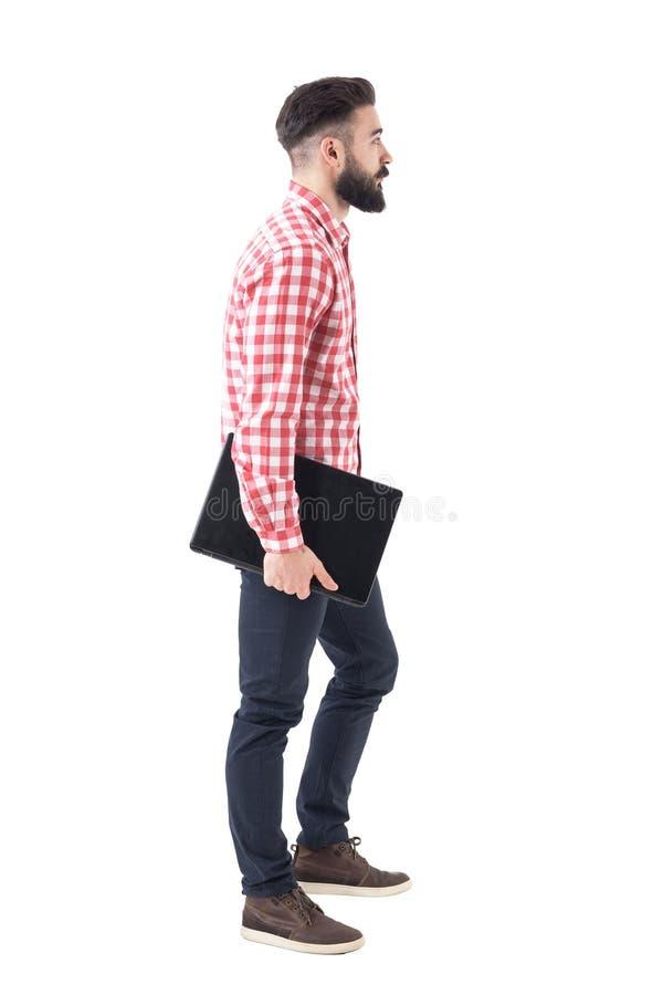 Vue de côté d'ordinateur portable de marche et de transport millénaire barbu élégant moderne d'homme d'affaires sous le bras photo libre de droits