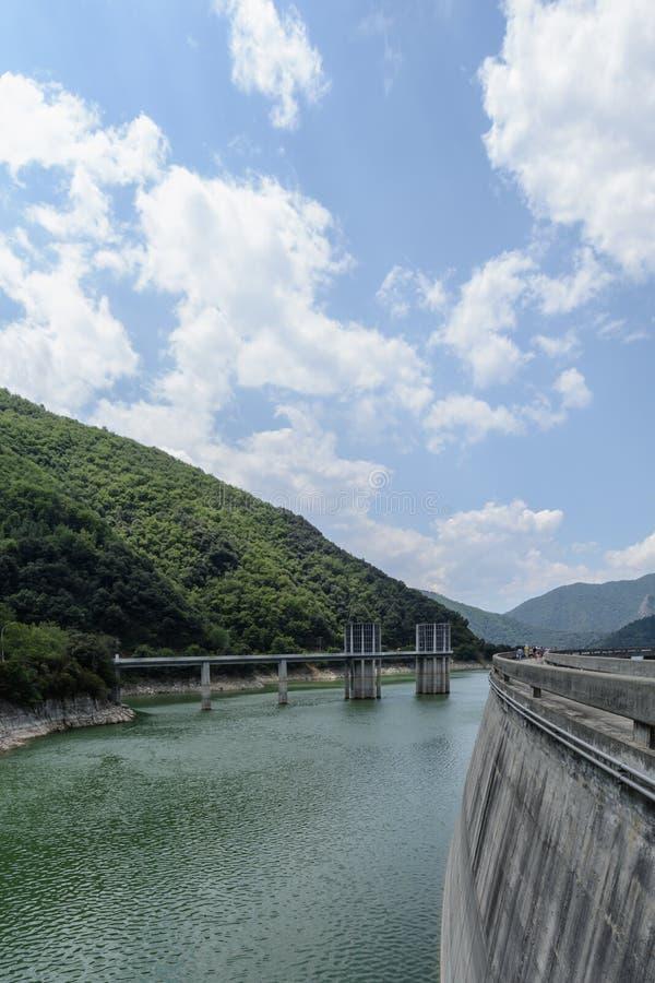 Vue de côté d'un barrage avec une forêt et des nuages de montagne photo stock
