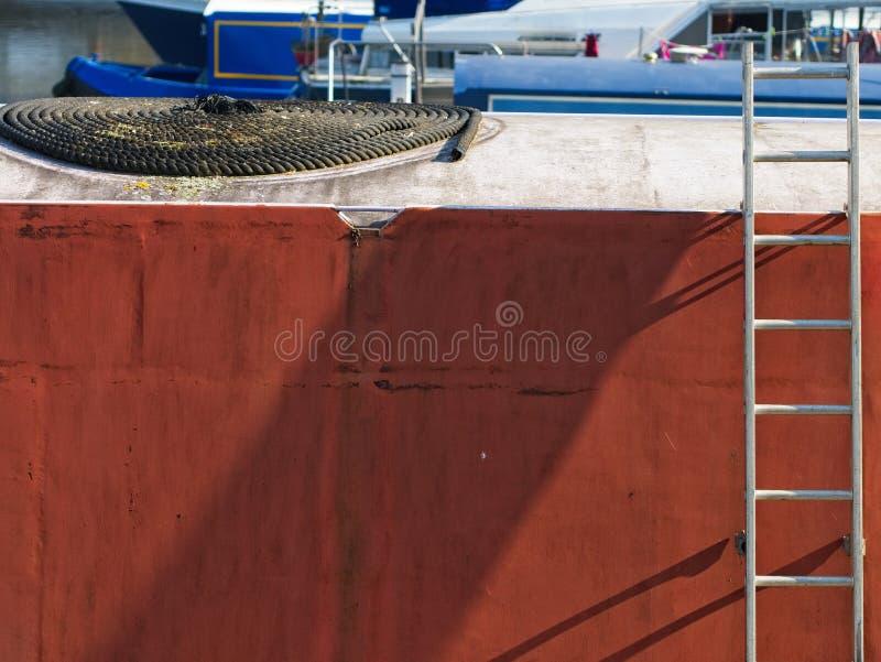 Vue de c?t? d'un bateau de couleur de terre cuite avec une ?chelle et une ligne d'amarrage sur le dessus de toit blanc photos libres de droits