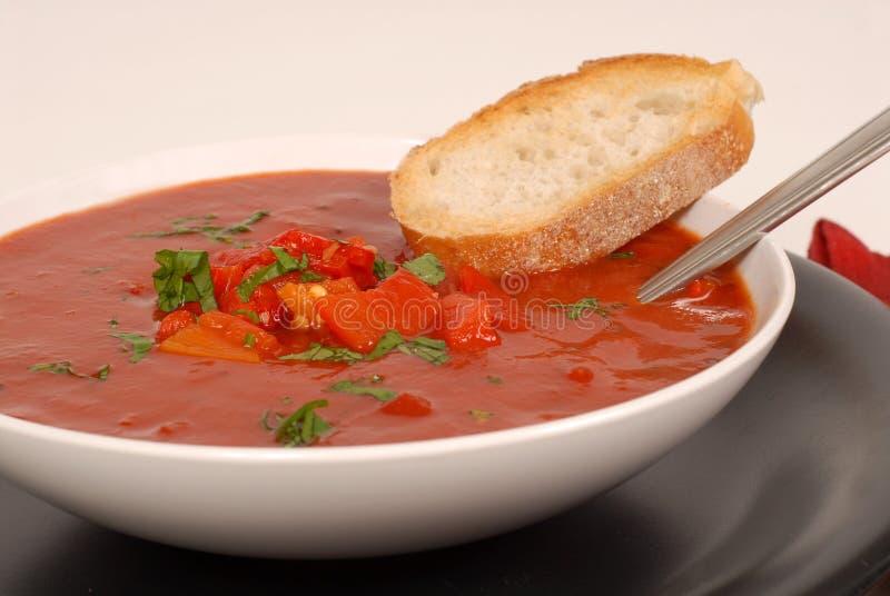 Vue de côté d'un bol de tomate, de poivron rouge et de potage de basilic avec du Br photos stock