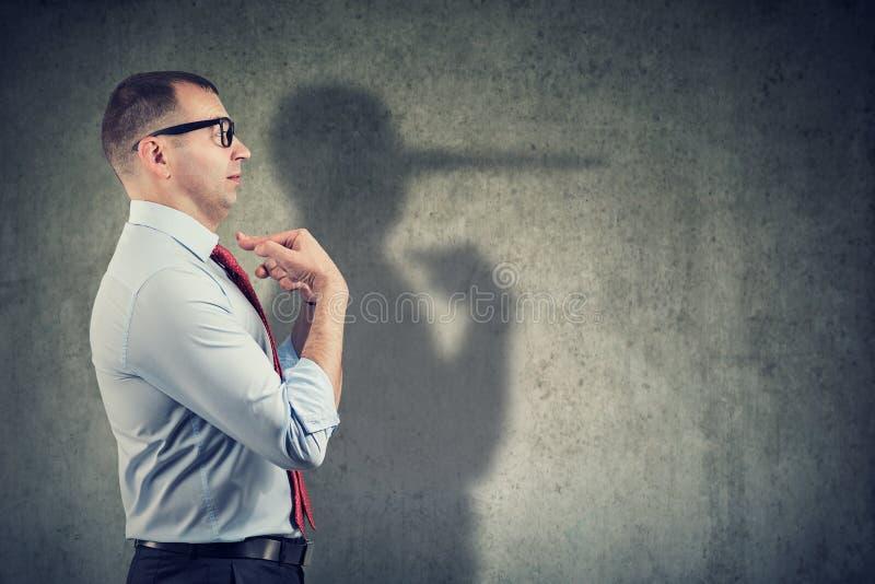 Vue de côté d'un homme d'affaires semblant étonné en étant propagé le mensonge image stock
