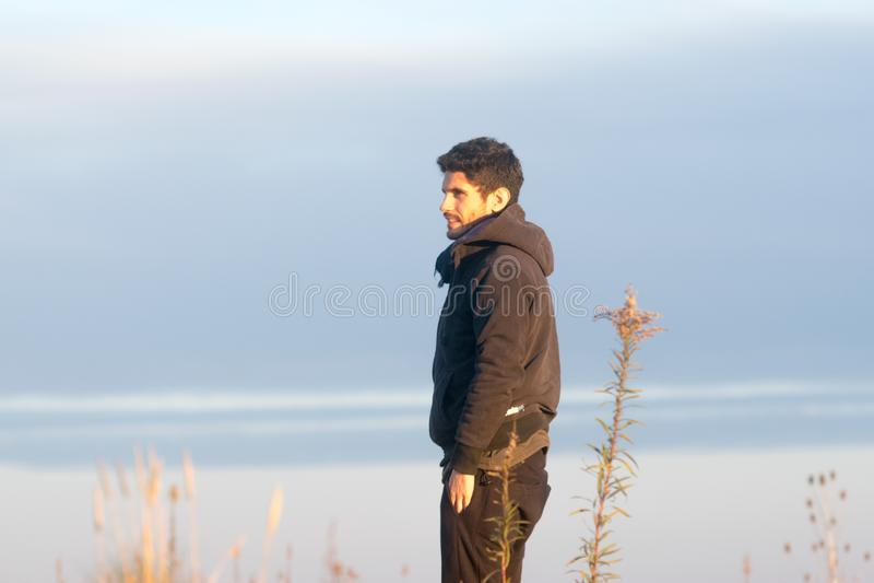 Vue de côté d'un homme regardant l'horizon le coucher du soleil image libre de droits