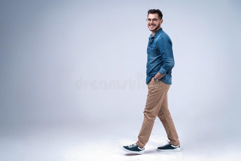 Vue de côté d'un jeune homme occasionnel de sourire marchant, sur le fond gris photographie stock