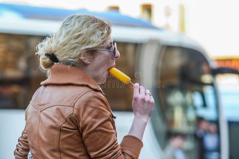 Vue de côté d'une femme mangeant l'extérieur de crème glacée de fruit Touristes marchant autour de Moscou photo stock