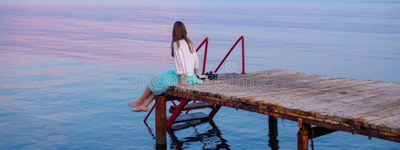 Vue de côté d'une jetée en bois sur la mer au coucher du soleil avec la jeune femme image stock