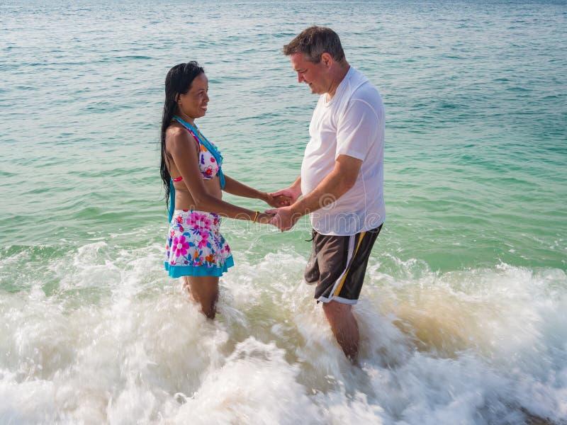Vue de côté d'une position de couples en mer photos stock