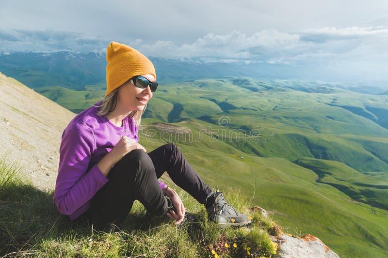 Vue de côté d'une position de touristes femelle attrayante sur les lunettes de soleil de port d'une colline herbeuse Appréciant u images stock