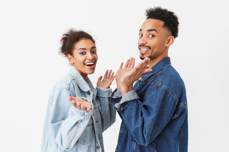 Vue de côté des couples heureux dans des chemises de denim posant ensemble images stock