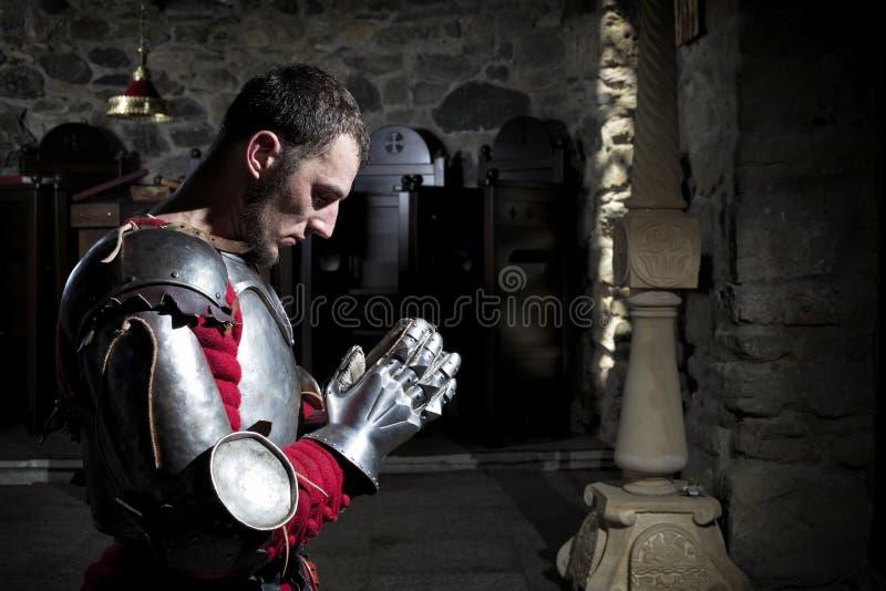 Vue de côté des genoux de Kneeling On His de chevalier avec la tête cintrée et les mains de prière photo libre de droits