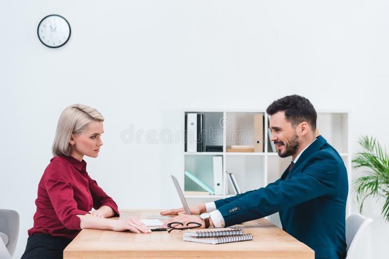 vue de côté des gens d'affaires regardant l'un l'autre tout en se reposant images stock
