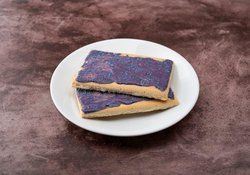 Vue de côté des pâtisseries de grille-pain de saveur de baie sur un plat blanc photos stock