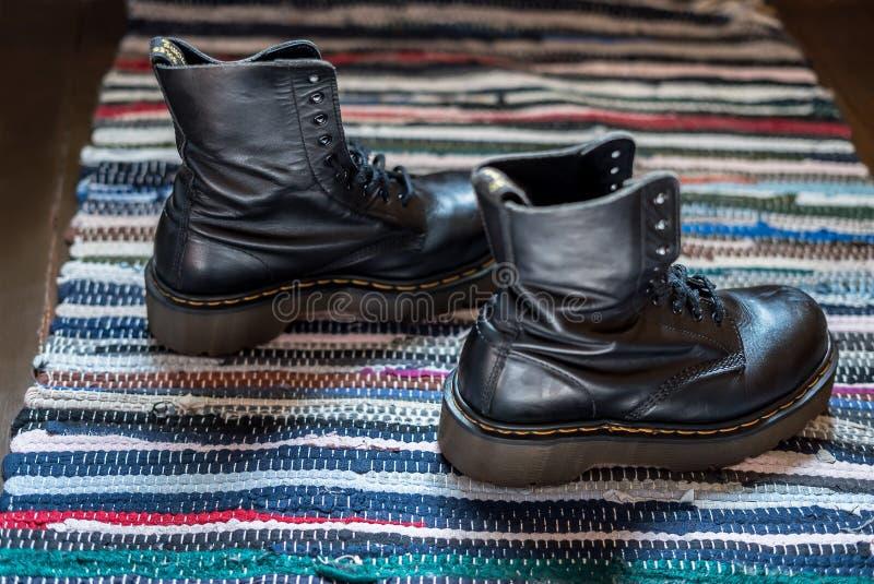 Vue de côté de deux robustes, bottes en cuir de cheville noire sur une couverture colorée photographie stock libre de droits
