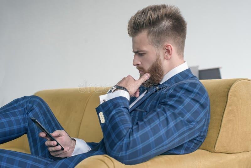 Vue de côté du bel homme d'affaires sexy s'asseyant sur un sofa dans un costume et à l'aide de son téléphone images stock