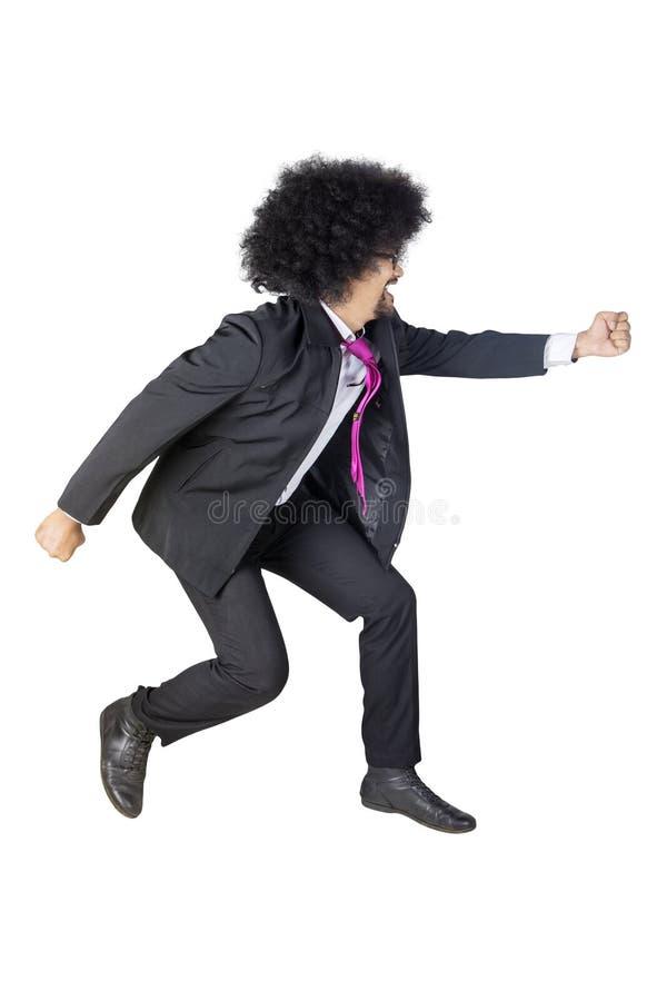 Vue de côté du fonctionnement d'homme d'affaires d'Afro sur le studio photo stock