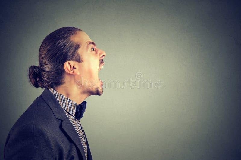 Vue de côté du hurlement fâché d'homme d'affaires images libres de droits