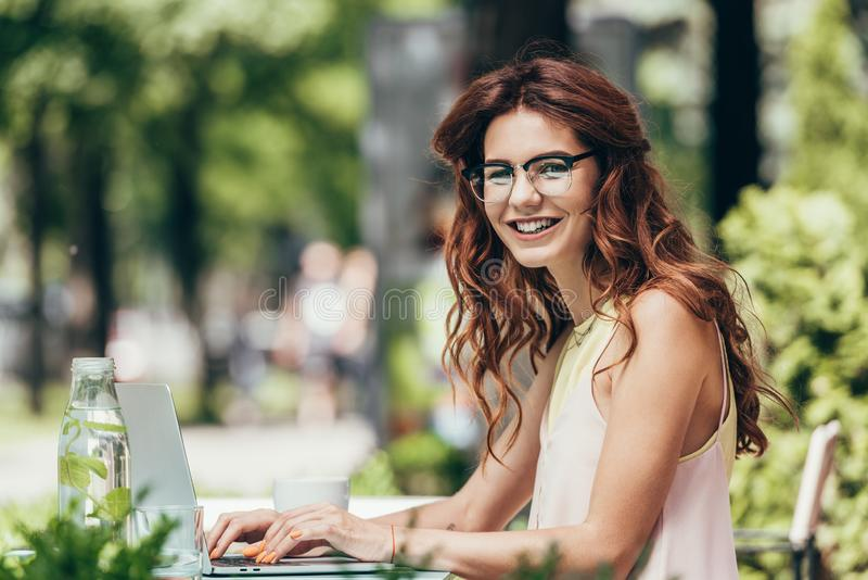 vue de côté du jeune blogger de sourire regardant la caméra tout en travaillant sur l'ordinateur portable image stock