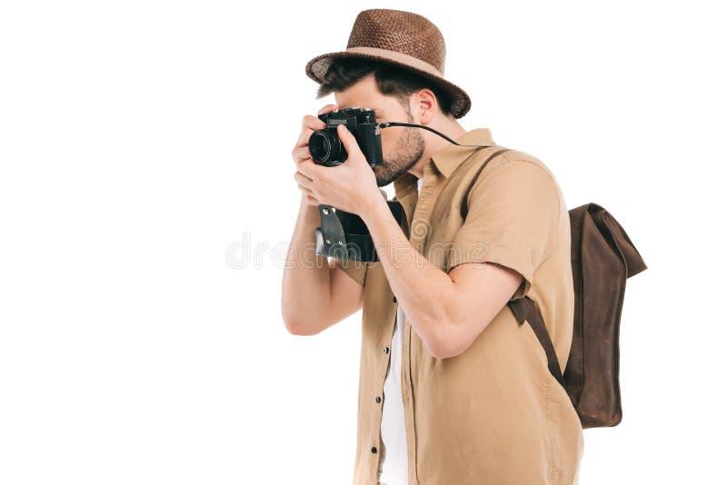 vue de côté du jeune homme avec le sac à dos photographiant avec la caméra photo stock