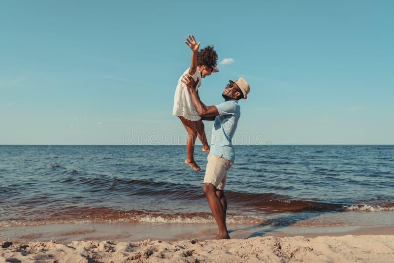 vue de côté du père heureux d'afro-américain jouant avec la petite fille mignonne photo libre de droits