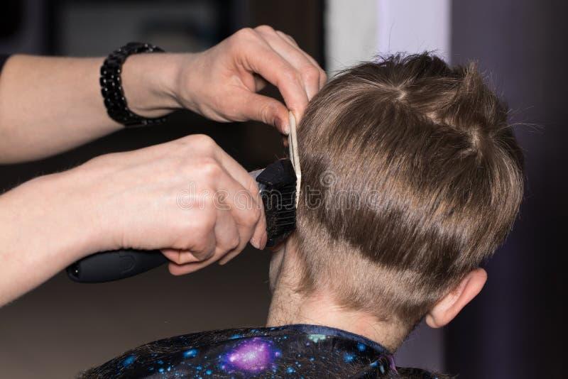 Vue de côté du petit garçon mignon obtenant la coupe de cheveux par le coiffeur à t image libre de droits